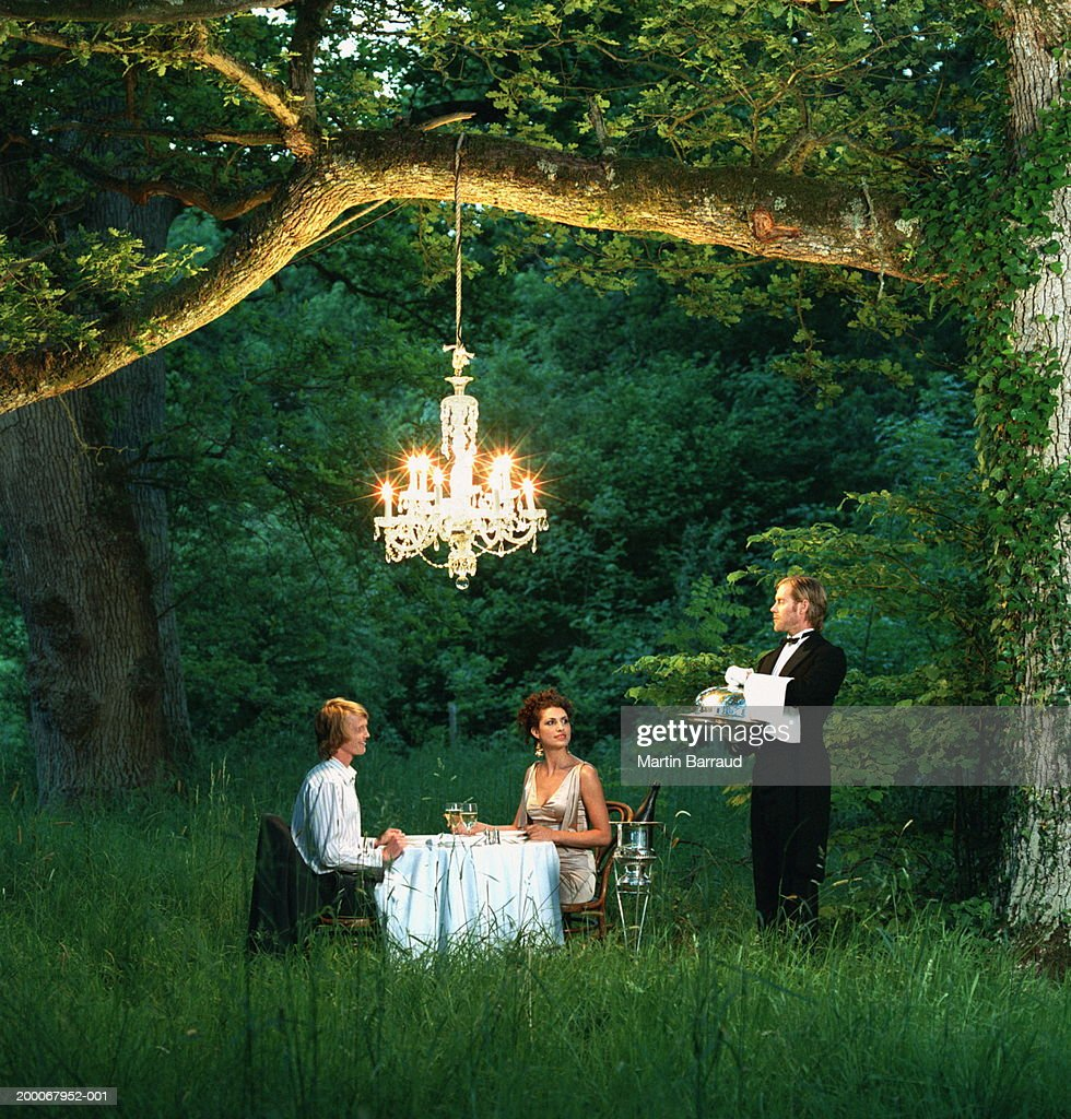 Butler waiting on young couple dining at table in forest : Stock Photo