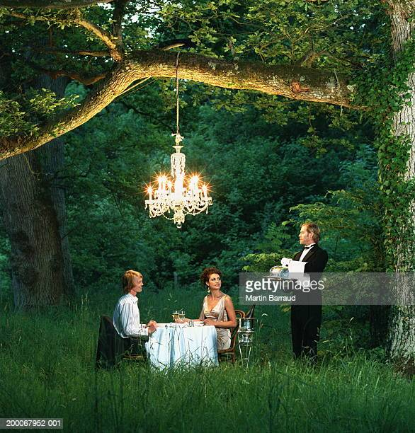 Butler waiting on young couple dining at table in forest