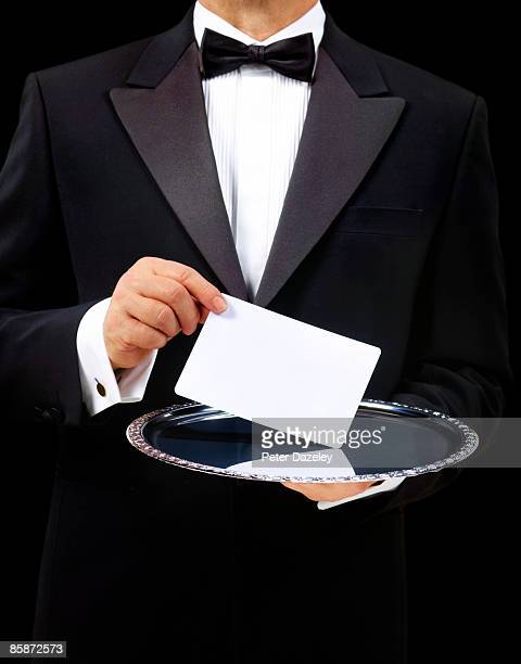 Butler with blank card on silver serving tray.