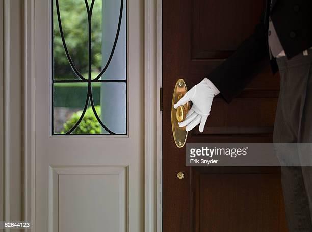 Butler with hand on front door knob.