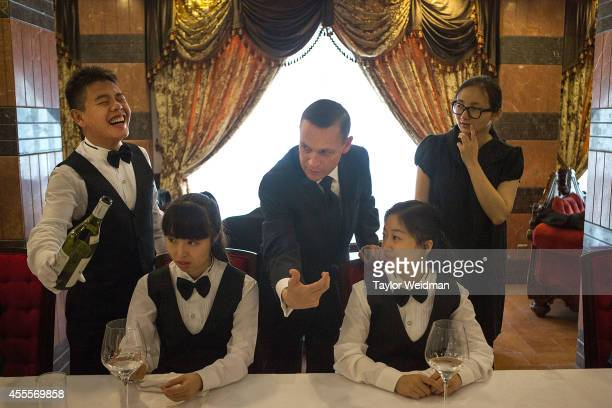 A butlery student laughs after making a mistake while being taught how to properly pour wine at The International Butler Academy China on September...