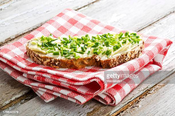 Butter and chives on whole grain bread, close up