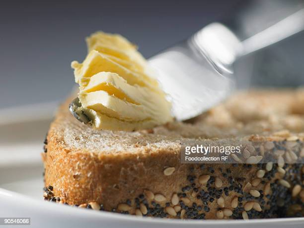 Butter knife with butter on seed bread, close up