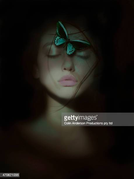 Butterfly perched on mixed race woman's face