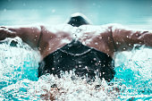 Butterfly stroke swimmer from back. Focus on water ripple