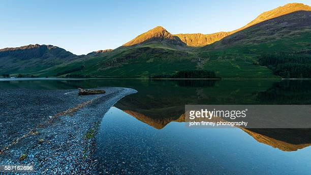Buttermere Lake on at sunrise with High Stile, Red Pike and Haystacks mountains catching the first light of the day. Lake District National park. UK. Europe.