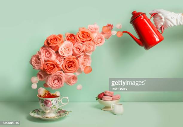 Buttler pouring a stream of roses into tea cup.