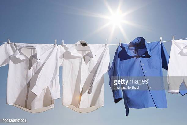 Button down shirts hanging from clothesline outdoors, low angle view