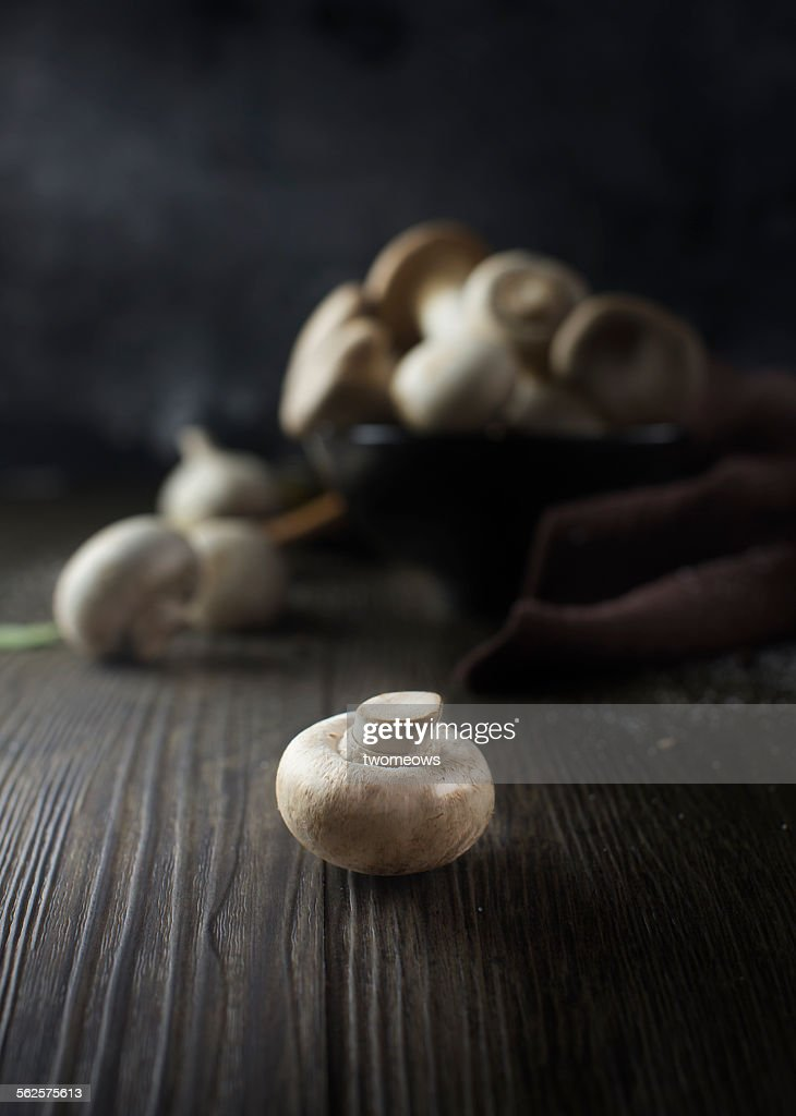 Button mushroom on wooden table.