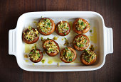 Button, portobello mushrooms stuffed with cheese and herbs with olive oil in a baking dish