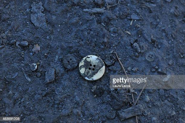 A button used for clothes is seen on the ground next to the clothing factory after the fire where seven Chinese workers died burned alive on December...