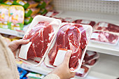 Buyer hands with beef meat packages at the grocery store