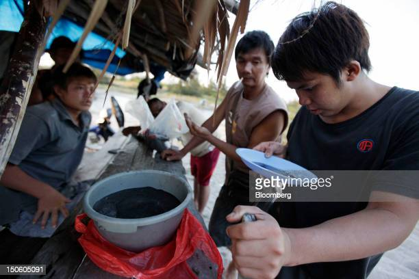 A buyer inspects the quality of tin ore being sold by a miner in Sungai Liat Bangka Island Indonesia on Friday July 27 2012 In recent years about...