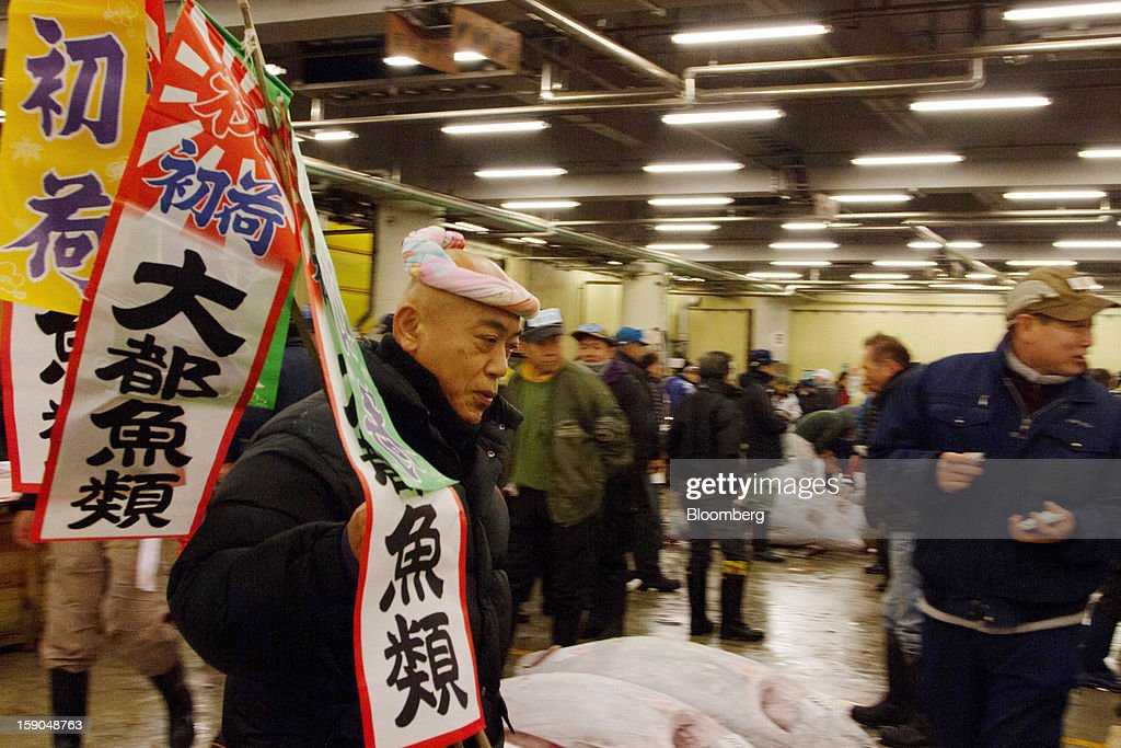 A buyer, left, carries flags as he prepares for the year's first tuna auction at Tsukiji Market in Tokyo, Japan, on Saturday, Jan. 5, 2013. Kiyomura K.K., a Tokyo-based sushi chain operator, outbid rivals for a second year in a row for the most expensive fish ever sold at the market, saying the purchase may help improve Japan-China relations. Photographer: Noriyuki Aida/Bloomberg via Getty Images