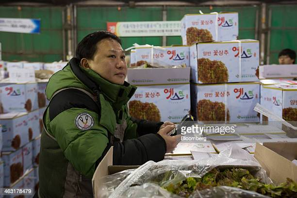 A buyer looks at a monitor displaying auction information unseen during a vegetable auction at Garak Market operated by Seoul AgroFisheries Food Corp...