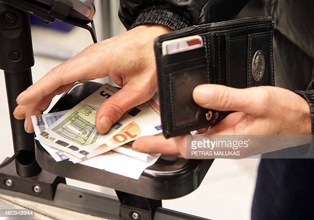 A buyer picks up euro coins in a supermarket in Vilnius on January 1 2015 AFP PHOTO / PETRAS MALUKAS