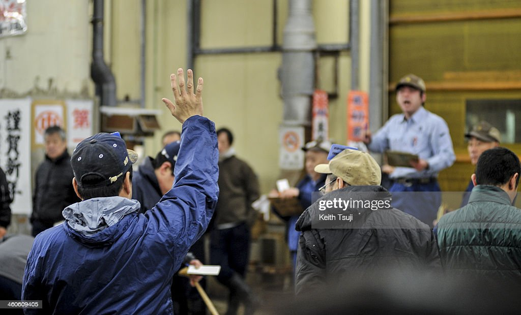A buyer raises his hand and makes a bid on the year's first auction at Tsukiji Fish Market on January 5, 2014 in Tokyo, Japan. Tsukiji Fish Market is best known as one of the world's most famous fish markets, handling thousands of tons of seafood daily.