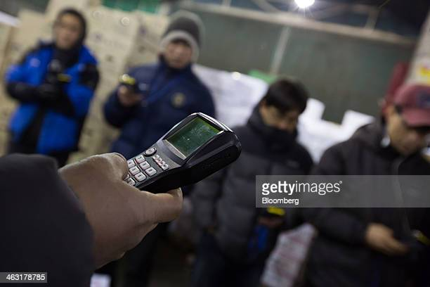 Buyers place bids using a wireless terminal during a vegetable auction at Garak Market operated by Seoul AgroFisheries Food Corp in Seoul South Korea...