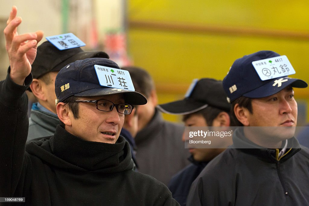 Buyers take part in the year's first tuna auction at Tsukiji Market in Tokyo, Japan, on Saturday, Jan. 5, 2013. Kiyomura K.K., a Tokyo-based sushi chain operator, outbid rivals for a second year in a row for the most expensive fish ever sold at the market, saying the purchase may help improve Japan-China relations. Photographer: Noriyuki Aida/Bloomberg via Getty Images