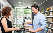 Man buying books and bookstore female owner.