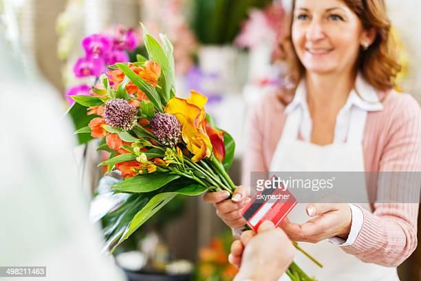 Buying flower in a flower shop.