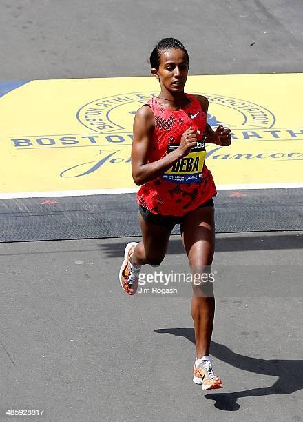 Buzunesh Deba of Ethiopia crosses the finish line of the 118th Boston Marathon on April 21 2014 in Boston Massachusetts