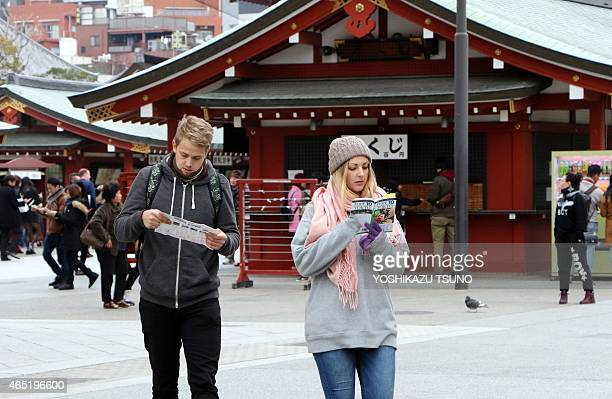 STORY by Anne BEADE This picture taken on March 3 2015 shows foreign tourists looking at a guide book and a map at Sensoji temple at Tokyo's Asakusa...