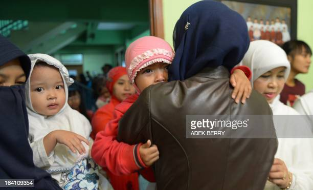 STORY by Arlina ARSHAD This picture taken in Bandung on February 10 2013 shows Indonesian mothers holding their daughters after they received a...