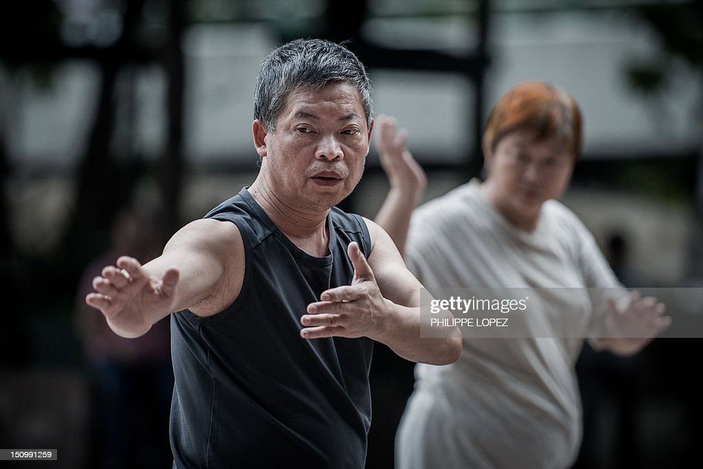 HEALTH' by Beh Lih Yi An elderly man and a woman practice Tai Chi in Hong Kong on August 30, 2012. Covered in smog and cramped apartment towers, Hong Kong is not usually associated with a healthy lifestyle, but new figures show that Hong Kongers are the longest-living people in the world. AFP PHOTO / Philippe Lopez