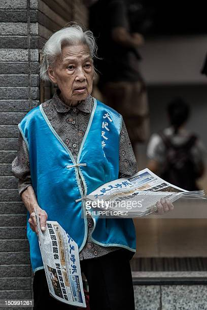 STORY 'HONG KONGLIFESTYLESOCIETYHEALTH' by Beh Lih Yi An elderly woman distributes newspapers in a street of Hong Kong on August 30 2012 Covered in...