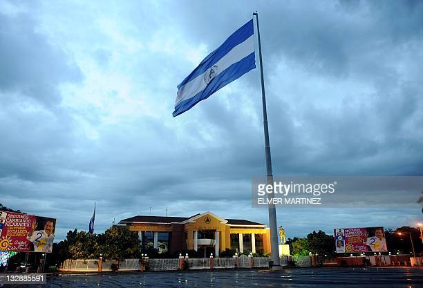 STORY by Blanca Morel The Nicaraguan national flag flutters at the front of the presidential palace known as the 'Casa de los Pueblos' in Managua on...