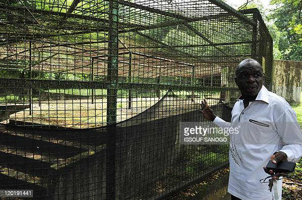STORY by Christophe KOFFI A picture taken on July 29 2011 shows Bruno Seka administrative manager of the Abidjan Zoo speaking in front of the empty...