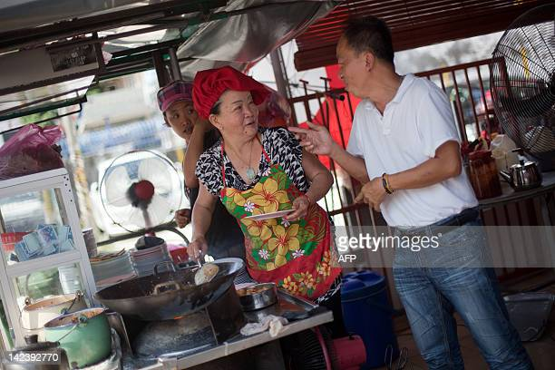 FEATURE by Dan Martin This photograph taken on February 23 2012 shows Soon Chuan Choo speaking with a customer as she prepares char kway teow in...
