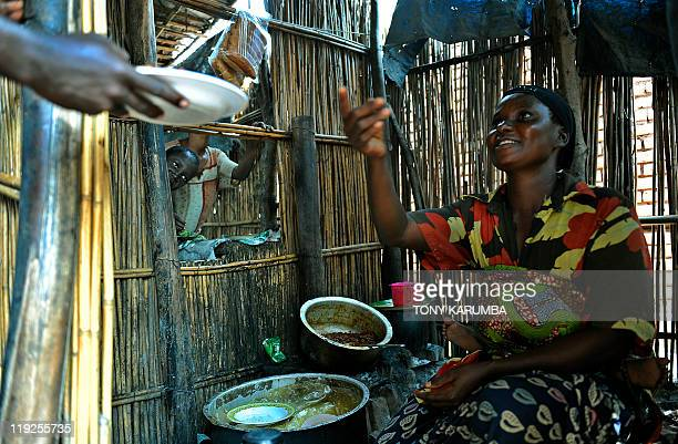 STORY by Emmanuel PEUCHOT Congolese woman Riziki Mapendo sits at her makeshift food stall where she sells boiled rice and beans in Democratic...