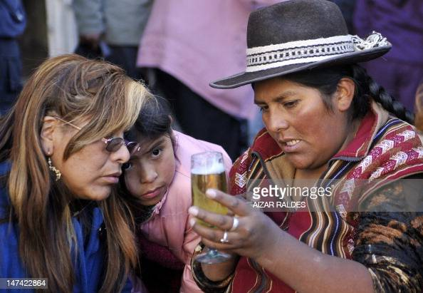 STORY by Gerardo Bustillos Andean fortuneteller Rosa Ticona reads a glass of beer with egg white to a woman at San Pedro square in La Paz on June 28...