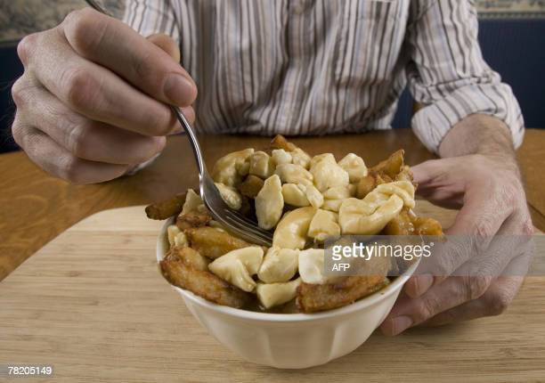 By Guillaume LAVALLEE CanadaUSAsocietygastronomy A man eats a popular Quebec dish called Poutine consisting of french fries cheddar cheese and gravy...