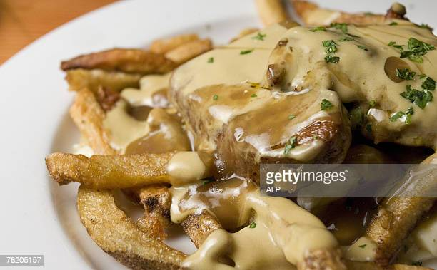 By Guillaume LAVALLEE CanadaUSAsocietygastronomy This Poutine au Fois Gras is prepared at Le Pied de Cochon 28 November 2007 in Montreal Quebec...