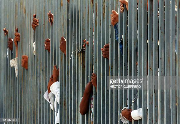 STORY by Hector Guerrero Catholics stand by a gate in the walled community of Nueva Jerusalem in Turicato Michoacan State Mexico on September 6 2012...