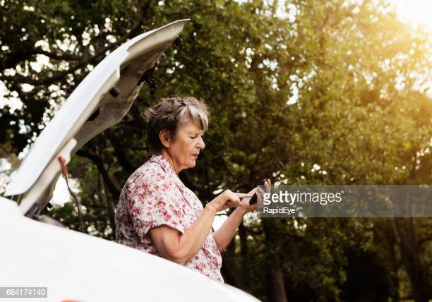 By her broken-down car, an old woman texts for assistance