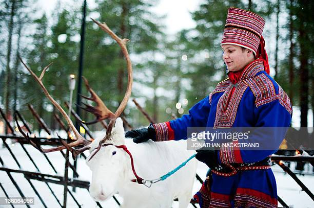 STORY by IGOR GEDILAGHINE FILES MORE IN IMAGE FORUM A man in traditional Laplander costume strokes a reindeer in the Santa Claus Village near...