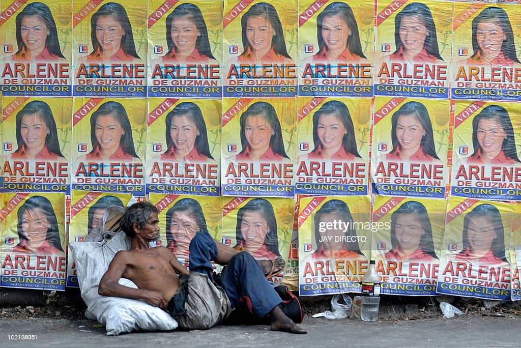 FOCUS by Jason Gutierrez (FILES) A homeless man sits with his paltry belongings in front of a wall covered with campaign posters of a politician running in the May election in the street of Manila on April 5, 2001. Such campaigning in slum areas of the capital are a standard practice for politicians in Philippine cities. Critics charge that politicians use these overcrowded squatter colonies as vote banks where they can count on huge numbers of votes in exchange for minor favours or even for cash.