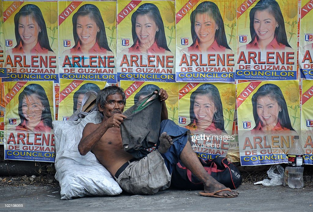FOCUS by Jason Gutierrez (FILES) A homeless man sits with his paltry belongings in front of a wall covered with campaign posters of a politician running in the May election in a street of Manila on April 5, 2001. Such campaigning in slum areas of the capital are a standard practice for politicians in Philippine cities. Critics charge that politicians use these overcrowded squatter colonies as vote banks where they can count on huge numbers of votes in exchange for minor favours or even for cash.
