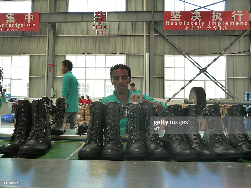 STORY by Jenny Vaughan A picture taken on April 19 2012 shows a worker lacing up boots on the assembly line at Huajian shoe factory in Dukem Ethiopia...