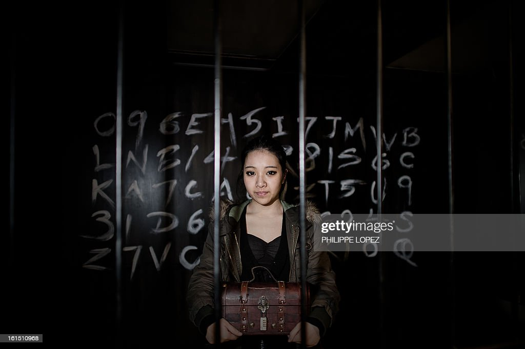 ESCAPE by Joe Sinclair In this picture taken on January 28, 2013, Elly Chau, 18, part of the Freeing HK staff holds a chest inside one of the rooms of the premises in Hong Kong. Freeing HK is a 'real escape game' in which players are pitted against a ticking clock as they desperately try to work their way out of the room by finding clues, cracking codes, and solving puzzles. AFP PHOTO / Philippe Lopez