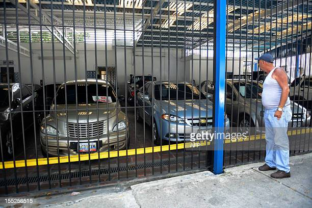 STORY by Jordi Miro A man looks at used cars at a car dealer in Caracas on October 30 2012 Venezuela the country with the largest oil reserves and...
