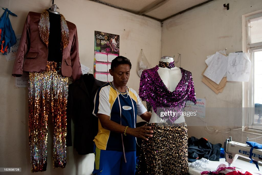 STORY by Jose Bautista Colombian worker Jhon Rusben seams a salsa dress in Cali, Colombia, on September 20, 2012. Thousands of people in Cali live from the salsa industry -- whether working at dance schools, tailors, showmakers, ballrooms and party rooms, or other related businesses. AFP PHOTO/Luis ROBAYO