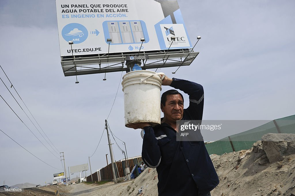 STORY by Juan Castro A man carries a bucket full of water as he walks near a billboard in Bujama, some 90 south of Lima, on March 15, 2013. At first glance the billboard is just one of many seen along the route leading to the beaches of the Asia District -- the most popular in Peru, bu the billboard has yet another use: it turns humidity into drinkable water that is used by locals. AFP PHOTO/ERNESTO BENAVIDES