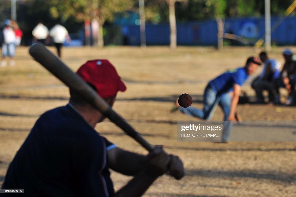 STORY by Julia Rios A man prepares to hit a ball while playing street baseball in Managua, on February 7, 2013. A group of men meets every afternoon in a park in the middle of the busy North Highway, in Managua, to play 'Bola Pasada' or 'Street Baseball' and make bets ranging between eight and 25 dollars per game. This sport is also known as 'Beisbol de Calcetin'(baseball sock) because it is played with balls made by hand out of pieces of garment to avoid damaging the windows of cars and houses around the park. AFP PHOTO/Hector RETAMAL