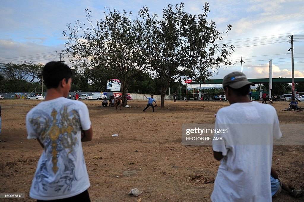 STORY by Julia Rios A pitcher (C) catches a ball during a game of street baseball, in Managua, on February 6, 2013. A group of men meets every afternoon in a park in the middle of the busy North Highway, in Managua, to play 'Bola Pasada' or 'Street Baseball' and make bets ranging between eight and 25 dollars per game. This sport is also known as 'Beisbol de Calcetin'(baseball sock) because it is played with balls made by hand out of pieces of garment to avoid damaging the windows of cars and houses around the park. AFP PHOTO/Hector RETAMAL