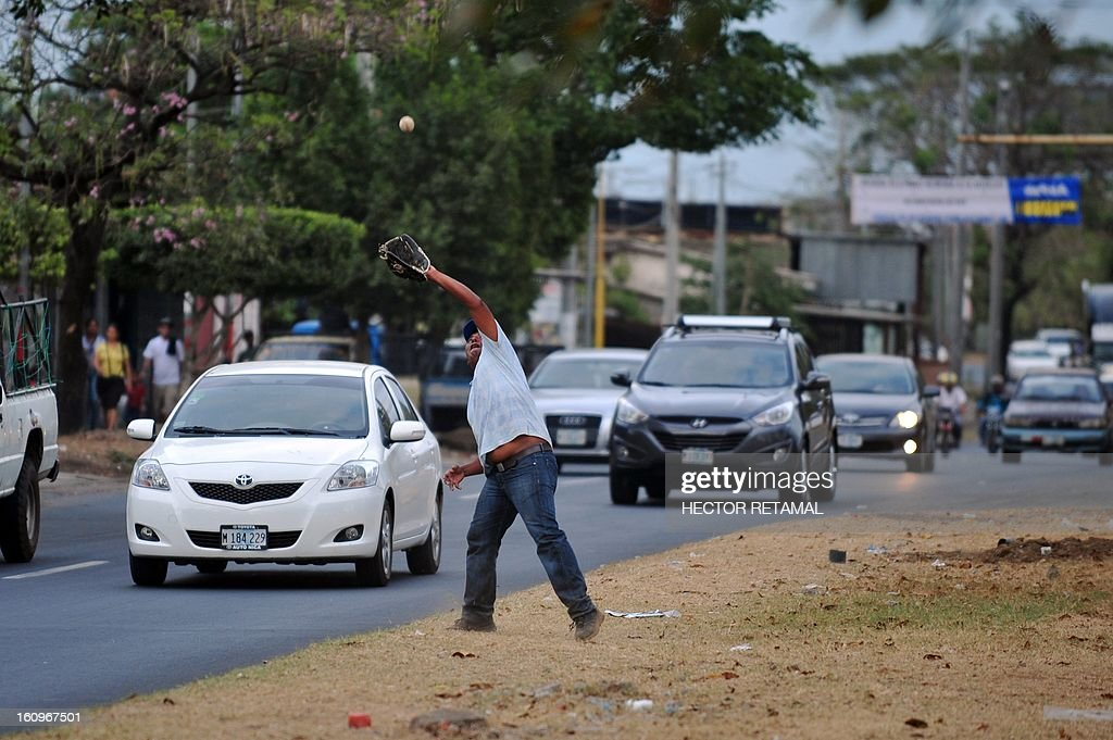 STORY by Julia Rios An outfield catches a ball during a game of street baseball, in Managua, on February 6, 2013. A group of men meets every afternoon in a park in the middle of the busy North Highway, in Managua, to play 'Bola Pasada' or 'Street Baseball' and make bets ranging between eight and 25 dollars per game. This sport is also known as 'Beisbol de Calcetin'(baseball sock) because it is played with balls made by hand out of pieces of garment to avoid damaging the windows of cars and houses around the park. AFP PHOTO/Hector RETAMAL